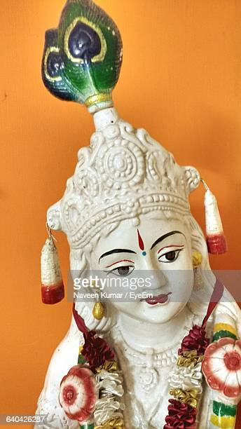 close-up of krishna statue against orange wall - lord krishna stock photos and pictures