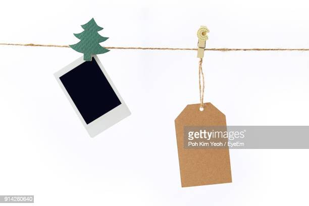 Close-Up Of Labels Hanging On Clothesline Against White Background