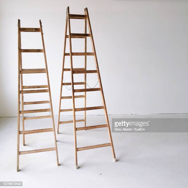 close-up of ladders against wall - step ladder stock pictures, royalty-free photos & images