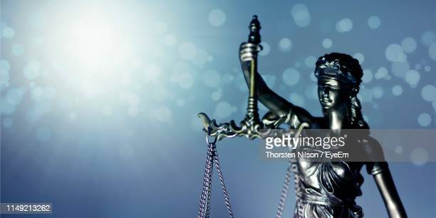 close-up of lady justice against illuminated background - justice concept stock pictures, royalty-free photos & images