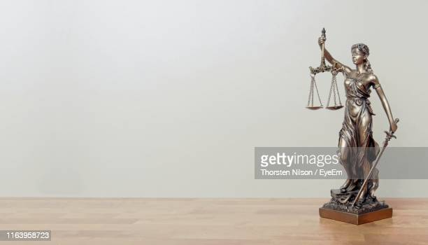 close-up of lady justice on table against wall - justicia fotografías e imágenes de stock