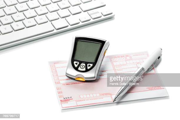 Close-Up Of Laptop With Mobile Phone By Pen And Paper Over White Background