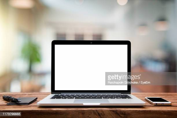 close-up of laptop with mobile phone on table in office - beeldscherm stockfoto's en -beelden