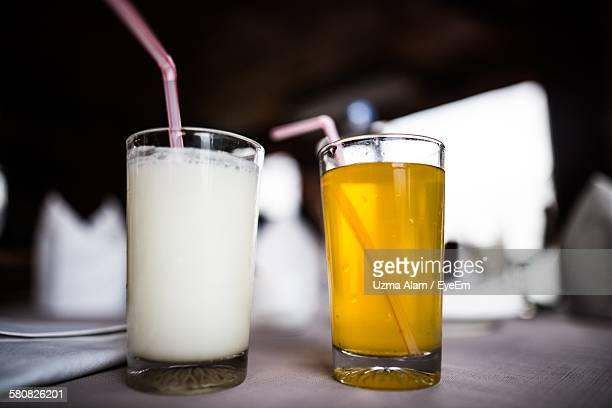 Close-Up Of Lassi And Orange Juice In Drinking Glass On Table