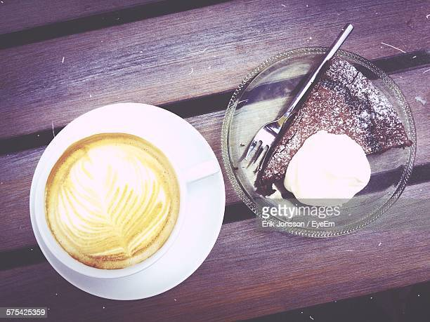 Close-Up Of Latte And Mud Cake On Bench
