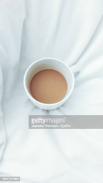 Close-Up Of Latte In Cup On Bed