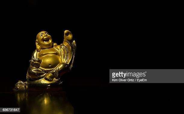close-up of laughing buddha against black background - buddha stock photos and pictures