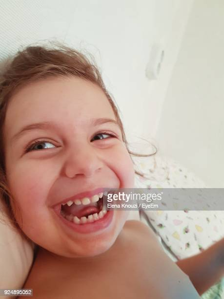 close-up of laughing girl lying on bed at home - elena knouzi stock pictures, royalty-free photos & images