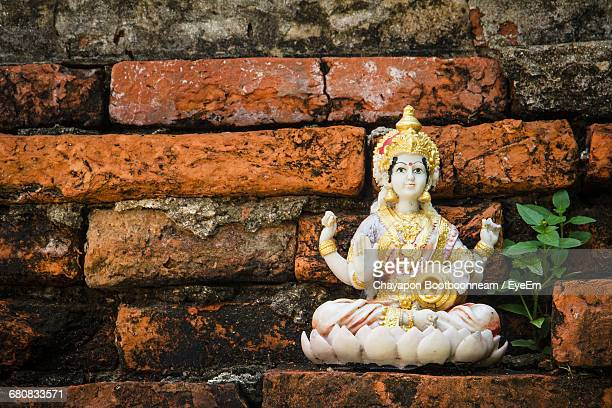 close-up of laxmi statue against red brick wall - goddess lakshmi stock photos and pictures