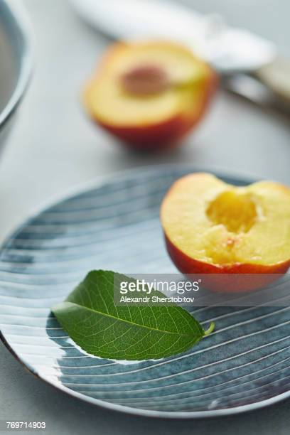 Close-up of leaf and halved peach in plate