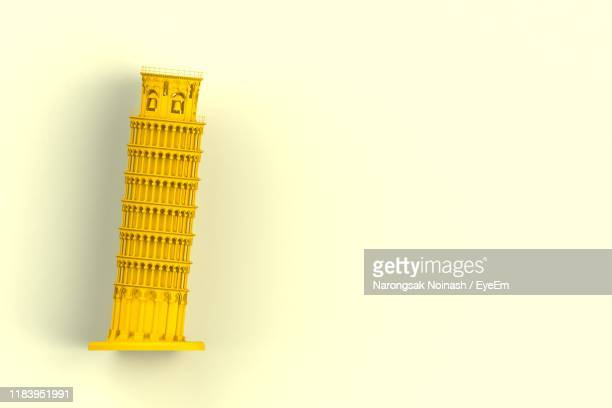 close-up of leaning tower of pisa souvenir against yellow background - souvenir stock pictures, royalty-free photos & images