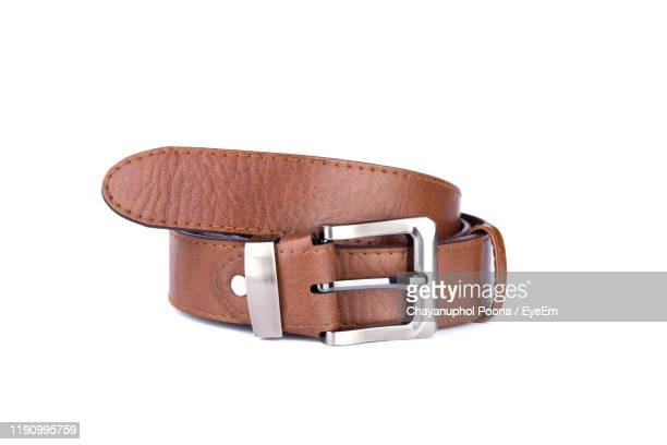close-up of leather belt over white background - belt stock pictures, royalty-free photos & images