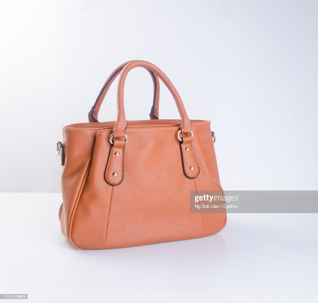 Close-Up Of Leather Purse On Table Against White Background : Stock Photo