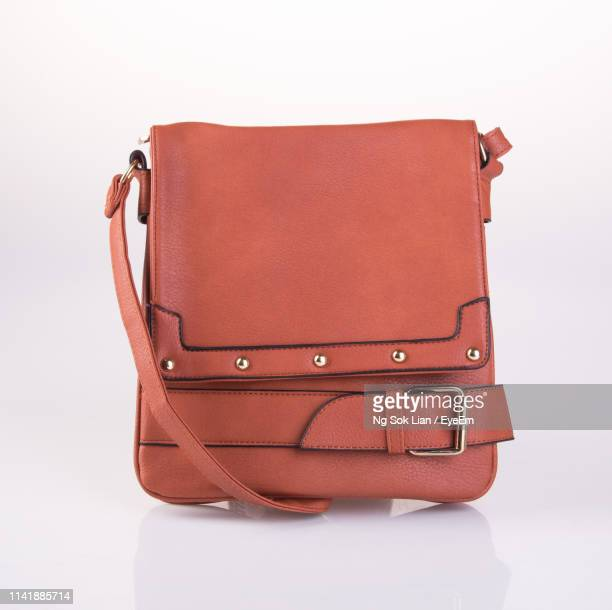 close-up of leather purse over white background - brown purse stock pictures, royalty-free photos & images
