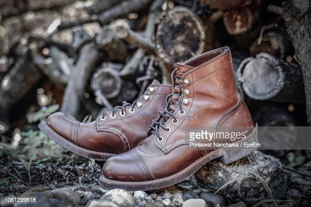 close-up of leather shoes against logs - bottes marron photos et images de collection