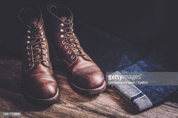 close-up of leather shoes with jeans on wooden floor - ブーツ ストックフォトと画像