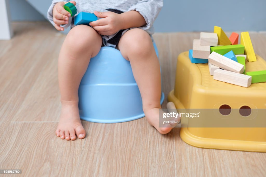 Closeup of legs of cute little Asian 18 months old toddler baby boy child sitting on potty playing with wooden blocks toy : Stock Photo