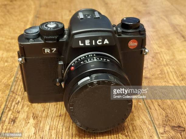 Close-up of Leica R7 film camera with 50mm prime lens on light wooden surface, November 27, 2019.