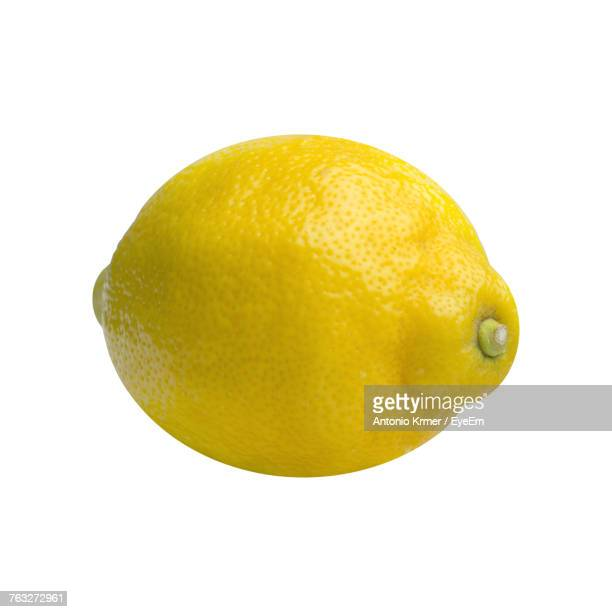 close-up of lemon against white background - zitrone stock-fotos und bilder