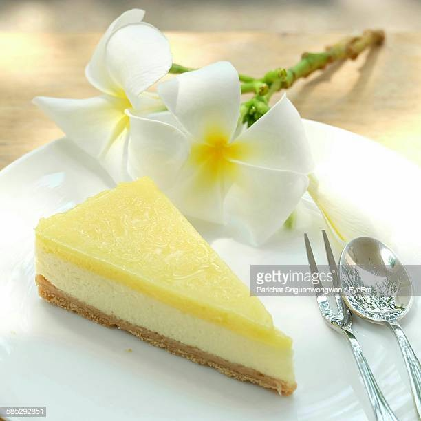 Close-Up Of Lemon Meringue Pie And Frangipanis On Plate