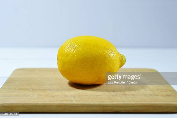 close-up of lemon on cutting board against white background - 後ろボケ ストックフォトと画像