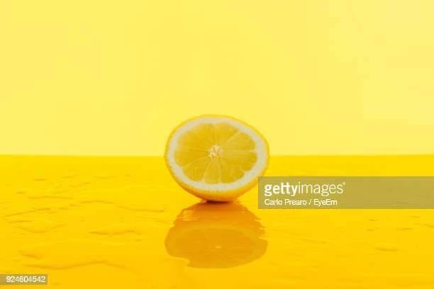 Close-Up Of Lemon On Table Against Yellow Background