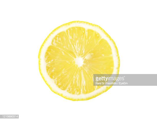 close-up of lemon slice against white background - zitrone stock-fotos und bilder