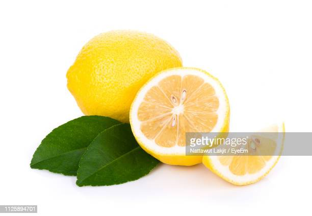 close-up of lemon slices against white background - zitrone stock-fotos und bilder