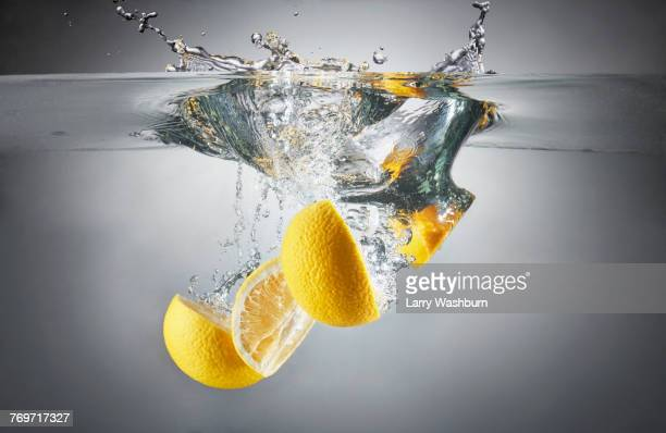 close-up of lemon slices in splashing water - slow motion stock pictures, royalty-free photos & images