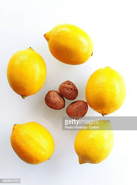 Close-Up Of Lemons And Walnuts On White Background