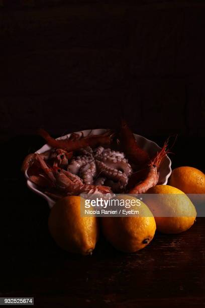 Close-Up Of Lemons By Seafood On Table Against Black Background
