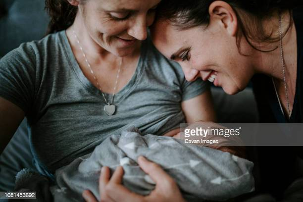 close-up of lesbian mothers with newborn son on bed at home - gay couple stock pictures, royalty-free photos & images