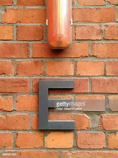 Close-Up Of Letter E And Lighting Equipment On Brick Wall