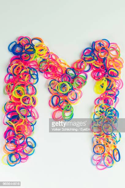 close-up of letter m made with colorful rubber bands over white background - letter m stock pictures, royalty-free photos & images