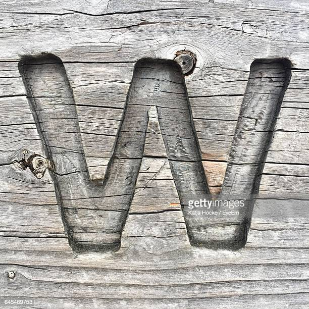 Close-Up Of Letter W Carved On Wood