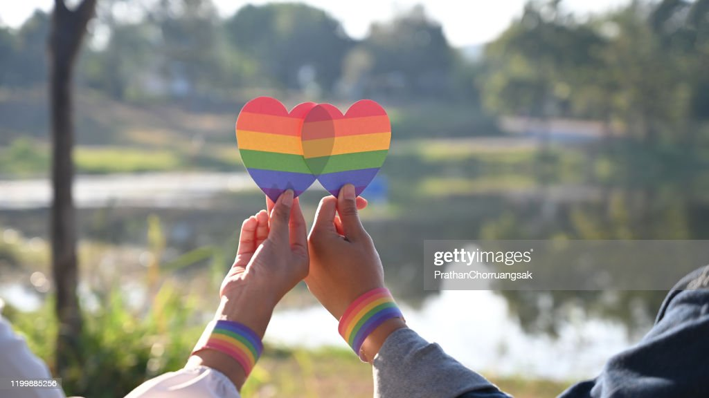 Closeup of LGBT couple while they are holding a rainbow hearts on hand. LGBT happiness concept. : Stock Photo