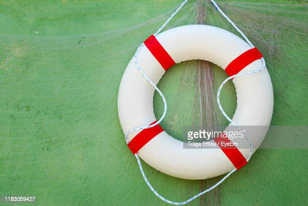 close-up of life belt hanging against wall - tolga erbay stock photos and pictures