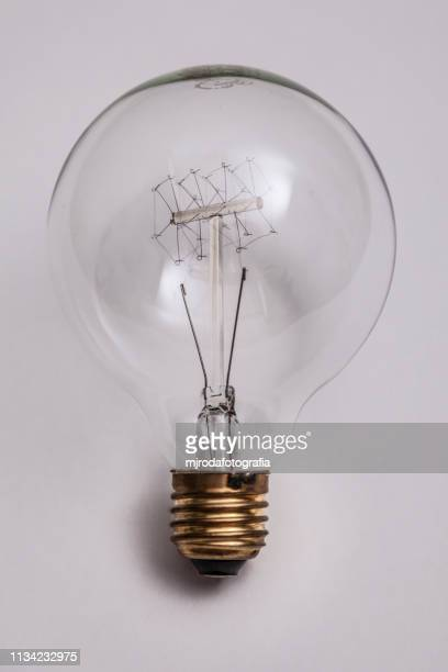 close-up of light bulb against white background - resplandeciente stock pictures, royalty-free photos & images