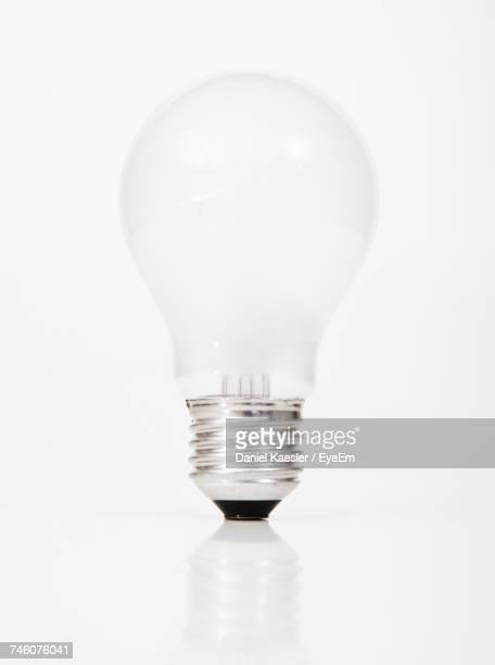 close-up of light bulb against white background - light bulb stock pictures, royalty-free photos & images