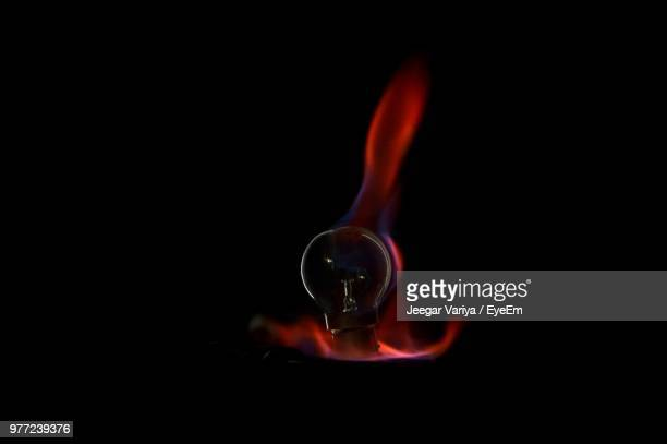 Close-Up Of Light Bulb And Flame Against Black Background