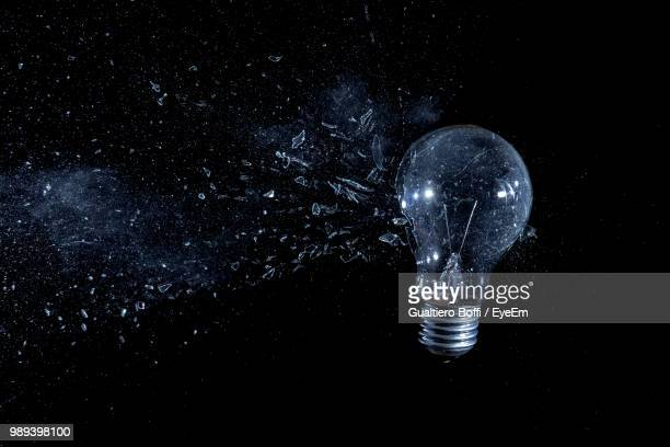 close-up of light bulb breaking against black background - filament stock photos and pictures