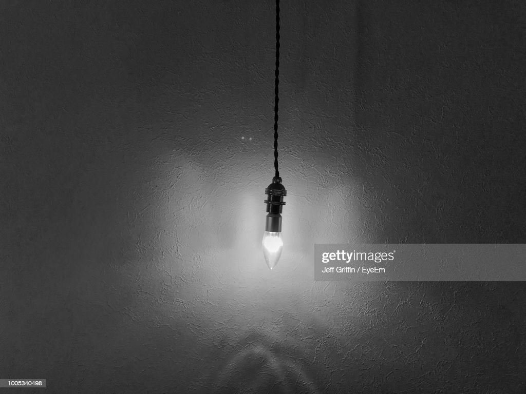 Closeup of light bulb hanging against wall stock photo getty images close up of light bulb hanging against wall stock photo aloadofball Gallery