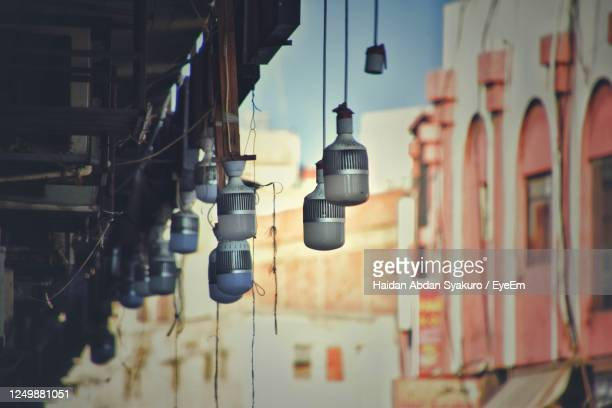 close-up of light bulb hanging on building - jeddah stock pictures, royalty-free photos & images