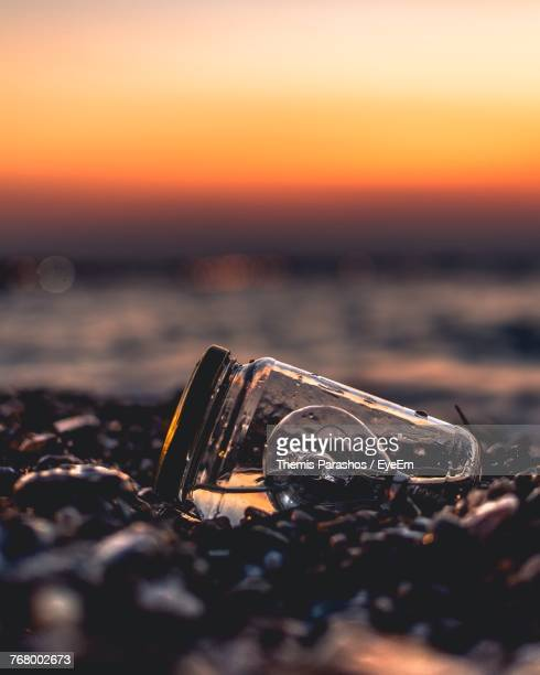 Close-Up Of Light Bulb In Jar At Beach During Sunset