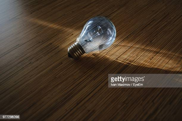 Close-Up Of Light Bulb On Wooden Table