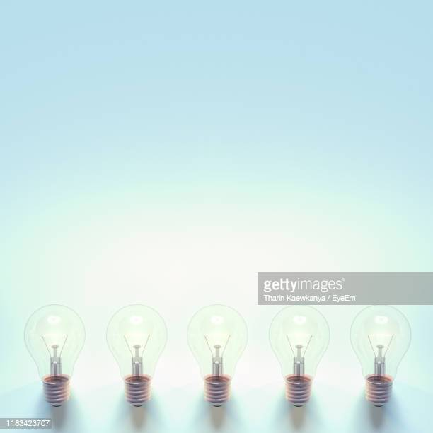 close-up of light bulbs against blue background - side by side stock pictures, royalty-free photos & images
