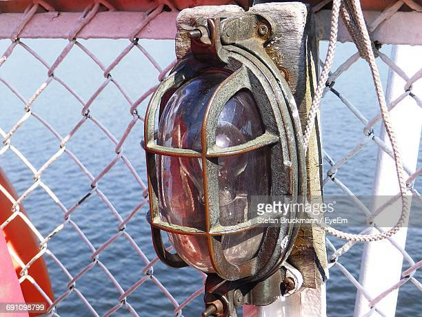 Close-Up Of Light Fixture On White Chainlink Fence Against Sea