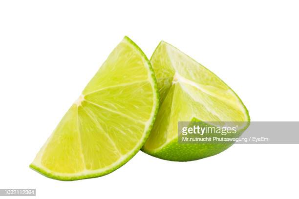 close-up of lime against white background - limette stock-fotos und bilder