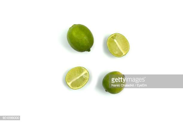 close-up of limes against white background - limette stock-fotos und bilder