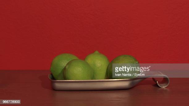 Close-Up Of Limes On Table By Red Wall